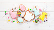 Easter greetings card with colorful gingerbread and sweets. On a white wooden background. Top view. Free space for your text.