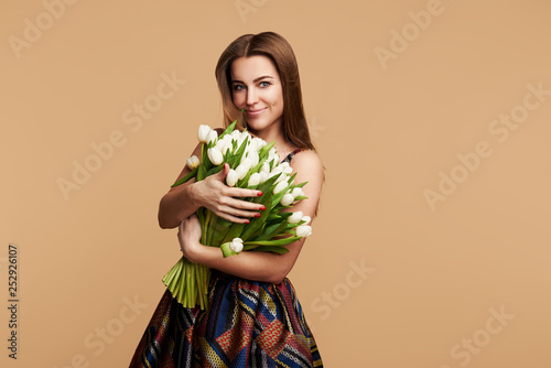 Wow effect. Wonderful flowers on Womens Day. Tender smiling brunet woman poses with white tulips, looks happily, isolated over beige studio background wall. Space for text
