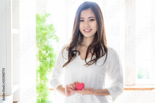 attractive asian woman holding heart symbol