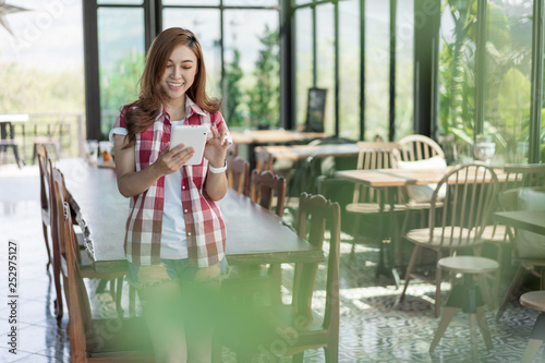 happy woman using digital tablet in cafe - 252975127