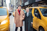 Fototapeta Nowy York - Happy young adult couple walking out from yellow taxi in New York City street for shopping © janifest