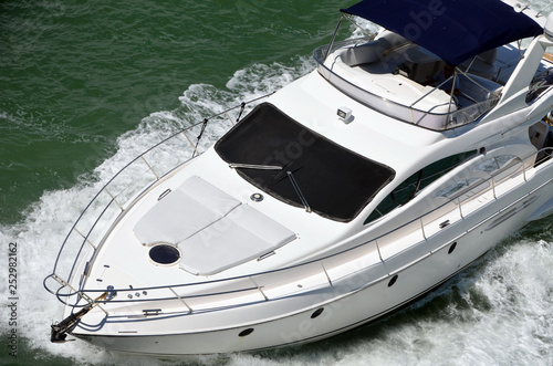 Close-up angled overhead view of a small white motor yacht  cruising the Florida Intra-Coastal Waterway off. Miami Beach