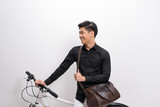 handsome young man with shoulder bag and bicycle standing isolated on white background