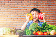 Happiness boy holding colorful sweet peppers with fresh vegetables on table