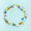 Easter eggs, purple and yellow flowers on pastel blue background. Spring, easter concept. Flat lay, top view, copy space, square