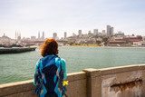 Young woman is looking at the San Francisco from a pier in San Francisco, United States of America.