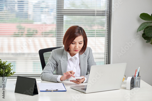 Asian businesswoman or accountant working pointing graph discussion and analysis data charts and graphs and using a calculator to calculate numbers. Business finances and accounting concept