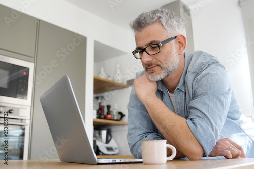 Man with computer at home in modern kitchen - 253055722