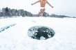Young man jumps and flies into the ice hole made on the winter lake