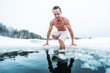 Young man with lean muscular body going to swim in the cold winter water with ice floating on the surface and forest on the background