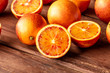 Leinwanddruck Bild - A closeup photo of vibrant organic blood oranges on a dark rustic background with copy space