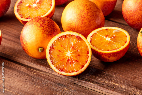 Leinwanddruck Bild A closeup photo of vibrant organic blood oranges on a dark rustic background with copy space