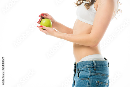 cropped view of slim young woman in big jeans holding green apple isolated on white