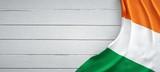 Irish flag, on top of white wood. Wrinkled fabric.