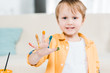 cute preschooler boy with colorful paint on hand looking at camera at home