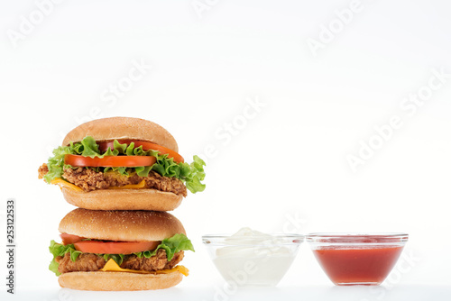 tasty chicken burgers near glass bowls with ketchup and mayonnaise isolated on white