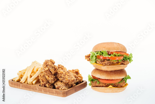 crispy chicken nuggets, chicken burgers and french fries isolated on white