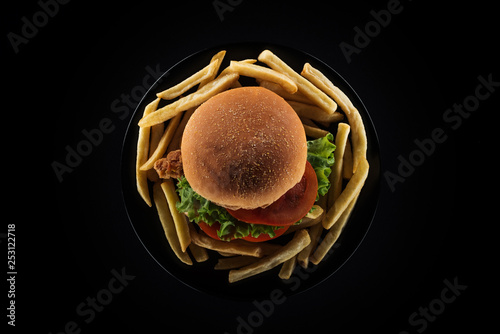 top view of tasty french fries and chicken burger on plate isolated on black