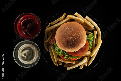 top view of tasty french fries and chicken burger near mayonnaise and ketchup isolated on black