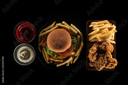 top view of tasty unhealthy meal isolated on black