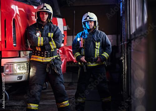 Leinwandbild Motiv Two firemen wearing protective uniform standing next to a fire engine in a garage of a fire department.