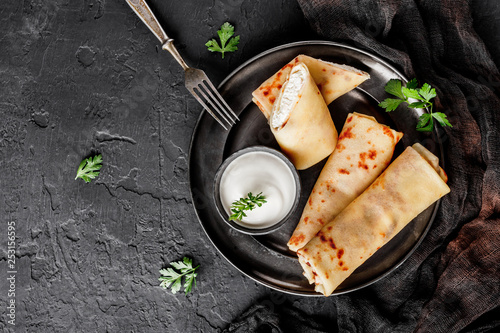 Crepes with cottage cheese, greens and sour cream on black plate over dark background. Pancake week or Shrovetide. Healthy breakfast. Top view, flat lay