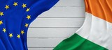 Flag of the European Union and Ireland, white wood background.