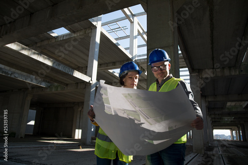 Male and female architects or business partners looking at floor plans on a construction site