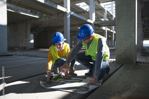 Male and female architects discussing over blueprint