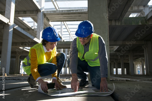 Two young architect going through construction plan details
