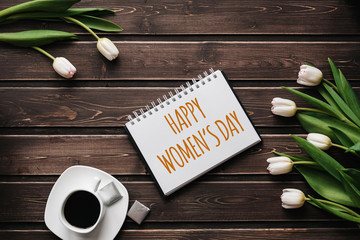 White Tulip flowers with a Cup of coffee on a wooden table. Greeting card with lettering Happy Women's Day