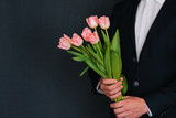 bouquet of pink tulips in the hands of a man