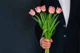 Fototapeta Tulipany - man's hand giving a bouquet of pink tulips © alexkoral