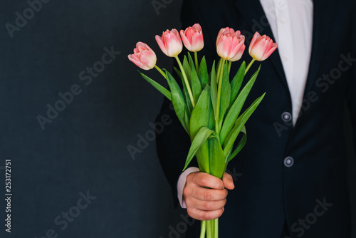 man's hand giving a bouquet of pink tulips