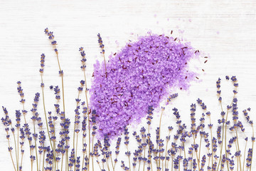 Essential lavender bath salt and lavender flowers on wooden background. SPA lavender products. Copy space