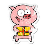 distressed sticker of a cheerful pig with christmas gift