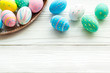 Easter traditions. Colorful Easter eggs in basket on white wooden background top view copy space