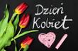 """Women's Day card and a bouquet of beautiful tulips on blackboard background, with Polish words """"Women's Day"""""""