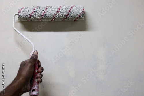 painting white paint on a wall with a roller brush. background with space for text