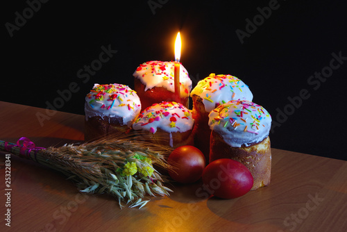 Easter. Traditional religious holiday. On the table are glazed Easter eggs, a lit candle, wheat and oats. Black background.