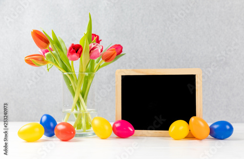 colorful tulips with chalkboard and easter eggs