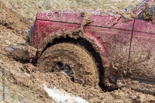 Car wheel slips in the dirt in nature - 253243381