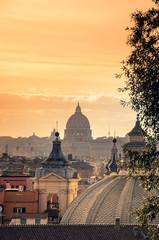 View from the top of Rome and the famous dome of the St. Peter's Basilica at sunset.