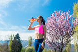 Woman having break from running drinking water