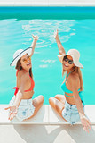 Two girls sitting by the pool, relaxing, having fun