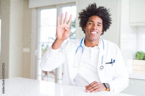 Leinwanddruck Bild African American doctor man at the clinic showing and pointing up with fingers number four while smiling confident and happy.