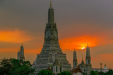 Fototapeta Paryż - Twilight wallpaper in the evening,the sun going back to the horizon,Wat Arun Ratchawaramaram is a temple along the ChaoPhraya River is an important place and a beautiful tourist destination in Bangkok © bangprik