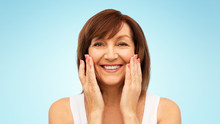 """Постер, картина, фотообои """"beauty, skin care and old people concept - portrait of smiling senior woman touching her face over blue background"""""""
