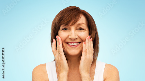 beauty, skin care and old people concept - portrait of smiling senior woman touching her face over blue background © Syda Productions