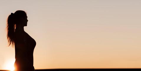 Silhouette einer Frau mit Pferdeschwanz Frisur im Gegenlicht